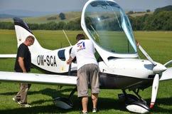 人在离开前检查小个人飞机并且为飞行做准备在草着陆带旁边 免版税库存图片