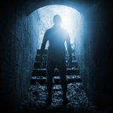 年轻人在黑暗的石隧道,被定调子的蓝色站立 库存图片