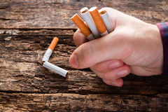 人在他的手上打破一根香烟 免版税库存照片