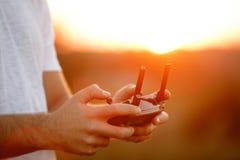 人在他的手上拿着一个寄生虫遥远的控制器 quadrocopter RC特写镜头在飞行期间的 飞行员拍空中照片 库存图片