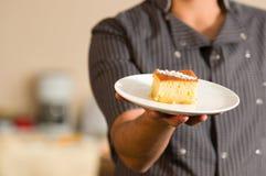 人在他的手上拿着与糖浆revani的可口土耳其酥皮点心在一块白色板材 免版税图库摄影