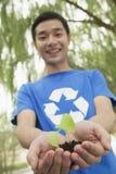 年轻人在他的手上的拿着幼木,回收标志,低角度视图 库存照片