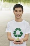 年轻人在他的手上的拿着幼木,回收标志,北京 免版税库存照片