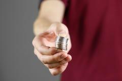 人在他的手上的拿着硬币 提供援助对照相机 库存照片