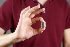 人在他的手上的拿着硬币 提供援助对照相机 免版税图库摄影