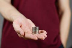 人在他的手上的拿着硬币 提供援助对照相机 图库摄影