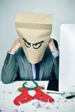 人在他的有一个纸袋的办公室在他的在圣诞节的头 免版税库存图片