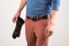 人在他的臀部附近拿着一台照相机 库存图片