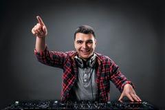 年轻人在dj的搅拌器的戏剧音乐在演播室 免版税库存照片