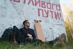 人在longboard,在一次愉快的旅途的墙壁上的题字旁边坐 库存图片