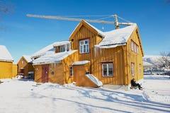 人在Skansen前面老木大厦坐在特罗姆瑟,挪威 图库摄影