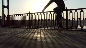 人在Slo Mo跳舞在一座现代桥梁的隐语在精采日落射线  股票视频