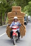 人在Ubud,海岛巴厘岛,印度尼西亚,关闭运输在一辆摩托车的物品在一条街道上  库存图片