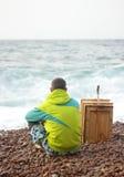 年轻人坐一个石海滩 免版税库存图片