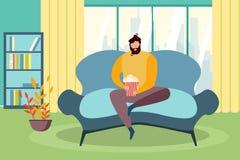 人坐与玉米花桶手表电视的长沙发窗口 皇族释放例证