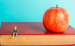 人坐书 教育的概念 苹果和书,蓝色背景,文本的地方,回到学校,拷贝空间 库存照片