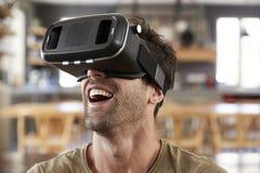 人坐佩带虚拟现实耳机的沙发 库存图片
