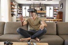 人坐佩带虚拟现实耳机的沙发 库存照片