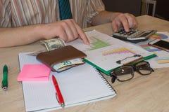 人坐在与计算器和企业辅助部件的桌上 免版税库存图片