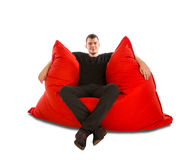 年轻人坐在丝毫隔绝的大红色装豆子小布袋沙发椅子 免版税图库摄影