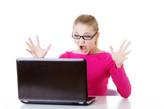 年轻人坐在膝上型计算机前面的惊奇的妇女。 免版税库存照片