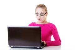 年轻人坐在膝上型计算机前面的惊奇的妇女。 库存图片