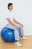 年轻人坐在医院健身房的锻炼球 免版税库存图片
