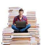 年轻人坐堆与膝上型计算机的书 免版税图库摄影