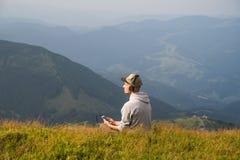 人坐小山的上面在喀尔巴阡山脉的并且听到在耳机的音乐并且享受美丽的景色 库存图片