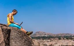 年轻人坐山有美丽的景色和与膝上型计算机一起使用 免版税库存照片