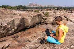 年轻人坐山有美丽的景色和与膝上型计算机一起使用 图库摄影