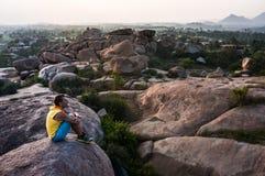 年轻人坐山有美丽的景色并且今后看 库存照片