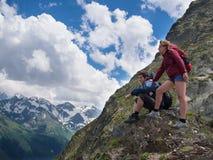 年轻人坐岩石在他旁边是有背包的一名妇女 免版税库存图片