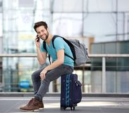 年轻人坐手提箱和叫由手机 库存照片