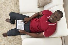 人坐拿着数字式片剂的长沙发 图库摄影