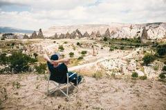 人坐椅子,放松并且敬佩卡帕多细亚小山的一个惊人的看法在土耳其 放松,休息 免版税库存照片
