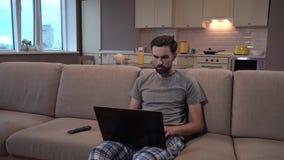 人坐沙发并且拿着膝上型计算机 他在家工作 集中人 他doesn ` t分散 人在屏幕上看和 影视素材