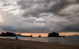 人坐海滩在日落以后 免版税库存照片