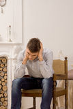 年轻人坐的认为在客厅 免版税图库摄影