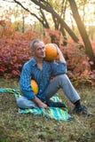 人坐盖子用两个巨大的南瓜 免版税库存照片