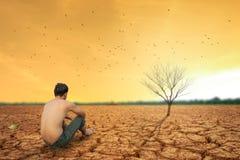 人坐破裂的地球在干陆附近 库存图片