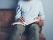 年轻人坐老沙发文字 免版税库存照片