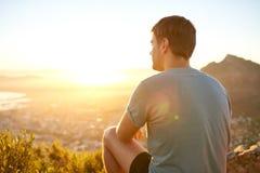 年轻人坐自然痕迹在日出 免版税库存图片