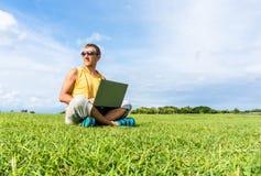 年轻人坐草和与膝上型计算机一起使用 免版税库存照片