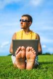年轻人坐草和与膝上型计算机一起使用 免版税图库摄影