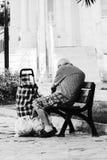 人坐长凳在购物以后 库存照片