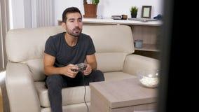 人坐长沙发并且打在控制台的一个电子游戏在客厅 股票录像