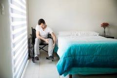 年轻人坐他的轮椅 免版税库存照片