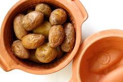 年轻人堆烘烤了在泥罐的土豆在白色 免版税库存照片