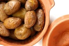 年轻人堆烘烤了在泥罐的土豆在白色 免版税图库摄影
